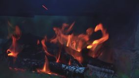 Charred wood in the fire. Burning wood in bright flames in the dark, close up, dynamic scene, toned video. 50fps stock video