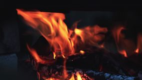 Charred wood in the fire. Burning wood in bright flames in the dark, close up, dynamic scene, toned video. 50fps stock footage