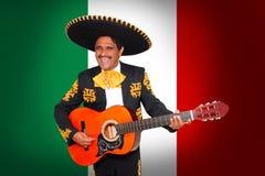 Charro Mariachi, der Gitarre in der Mexiko-Markierungsfahne spielt Stockfotografie