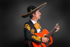 Charro Mariachi playing guitar on black. Background stock photos