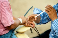 Charros horsemen binding their hands with tape. Two Mexican horsemen or riders sitting on their horses binding their hands with tape to prepare for a charros Royalty Free Stock Image