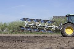 Charrue derrière le tracteur sur le champ néerlandais en Hollandes au printemps près d'Utrecht Images stock