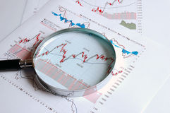 Chart. Examining stock chart with a magnifying glass Stock Photos