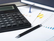Home savings, budget concept. Chart ,accounting books, pen, calculator on wooden office table. Chart,accounting books, pen, calculator on wooden office table Stock Image