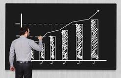 Chart on blackboard. Young businessman drawing chart on blackboard Royalty Free Stock Photos