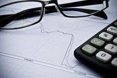 Chart, calculator, glasses as financial stock analysis concept Royalty Free Stock Photos