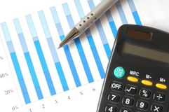 Chart with calculator and pen. A pen and calculator on top of a business chart Stock Photos