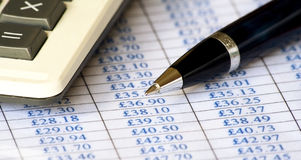 Chart, calculator & pen. Close up of a calculator & pen on top of a price chart Stock Images