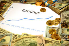 Chart of earnings rising up with money and gold. Chart of earnings rising up surrounded by money and gold royalty free stock photo
