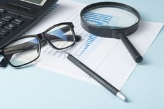 Home savings, budget concept. Chart ,glasses, pen, calculator and magnifying glass on wooden office table. Chart, glasses, pen, calculator and magnifying glass Royalty Free Stock Image