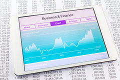 Chart or graph with stock market data application on tablet. Advanced chart or graph with stock market data application on a digital tablet and papers with royalty free stock photo