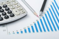 Home savings, budget concept. Chart. pen, calculator and coins on wooden office desk table. Chart, notepad, pen, calculator and coins on wooden office desk table Stock Images