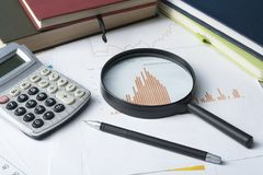 Home savings, budget concept. Chart , pen, calculator and magnifying glass on wooden office table. Chart, notepad, pen, calculator and magnifying glass on Stock Image