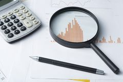 Home savings, budget concept. Chart , pen, calculator and magnifying glass on wooden office table. Chart, pen, calculator and magnifying glass on wooden office Stock Images