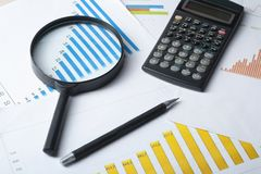 Home savings, budget concept. Chart , pen, calculator and magnifying glass on wooden office table. Chart, pen, calculator and magnifying glass on wooden office Royalty Free Stock Images