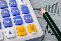 Chart, pencil and calculator. A sheet with chart and trend line, with a pencil and a calculator, means working and calculate Royalty Free Stock Photo