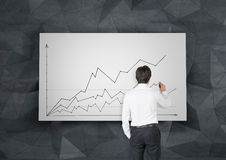 Chart of profits. Young businessman in room drawing chart of profits on poster Stock Photos