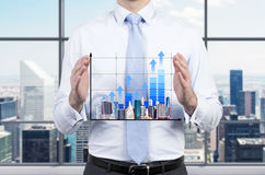 Chart and skyscraper in hand Stock Photography