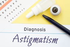 Chart for testing visual acuity, eye drops and eye anatomical model lies next to inscription Diagnosis Astigmatism. Concept for di. Agnosis, treatment and stock photo