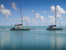 Charter boats moored inside the reef. MW: Two charter-boat, catamaran yachts, at anchor on the crystal clear water in Rarotonga, Cook Islands, South Pacific stock images