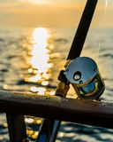 Sport fishing gear at sunset. Charter fishing rod and reel on a boat on the ocean or bay Royalty Free Stock Photo