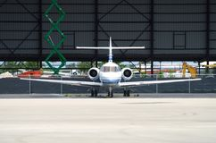 Charter plane. Front view of private jet parked in hangar royalty free stock images