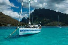 Charter yacht anchored off Mo'orea, Tahiti. A Charter yacht lies at anchor on the aqua blue Tahitian lagoon, in the shadow of the rugged mountain of Bali Hai royalty free stock image
