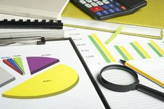 Charts, accounting books, calculator and magnifying glass on wooden office table. Financial and budget concept. Royalty Free Stock Image