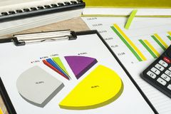 Charts, accounting books and calculator on wooden office table. Financial and budget concept. Stock Image