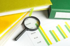Charts, accounting books and magnifying glass on wooden office table. Financial and budget concept. Royalty Free Stock Photography