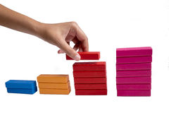 Charts of colored toy blocks with hand  on white background Royalty Free Stock Photography