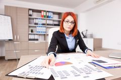 Charts and diagrams on the table. While a businesswoman is looking at them Royalty Free Stock Photography