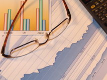 Charts and Glasses. Examining financial charts with glasses royalty free stock photography