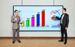 Charts on plasma panel. Two businessman in office and charts on plasma panel Stock Images
