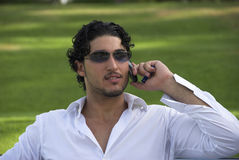 CHARTTING AWAY!. A YOUNG MAN CHATTING ON HIS CELLLPHONE Royalty Free Stock Image