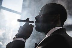 Charuto de fumo do homem afro-americano seguro dentro Imagem de Stock