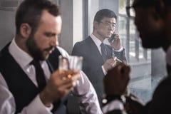 Charuto de fumo do homem de negócios asiático sério e fala no smartphone quando colegas que bebem o uísque Foto de Stock Royalty Free