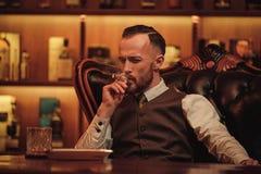 Charuto de fumo do homem seguro da classe alta no clube do ` s dos cavalheiros Fotografia de Stock