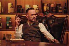 Charuto de fumo do homem seguro da classe alta no clube do ` s dos cavalheiros Fotografia de Stock Royalty Free