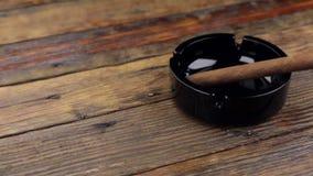 Charuto luxuoso em um cinzeiro em uma tabela de madeira do vintage tiro do slider vídeos de arquivo
