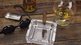 Charuto luxuoso, vidro do álcool e óculos de sol à moda em uma tabela de madeira do vintage Panorama vídeos de arquivo