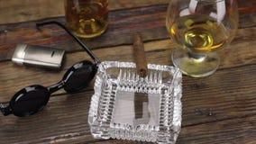 Charuto luxuoso, vidro do álcool e óculos de sol à moda em uma tabela de madeira do vintage rotação filme