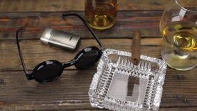 Charuto luxuoso, vidro do álcool e óculos de sol à moda em uma tabela de madeira do vintage tiro do slider vídeos de arquivo