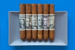 Charutos cubanos cinzentos do prato cerâmico e do luxo com banknot do dólar americano Fotografia de Stock Royalty Free