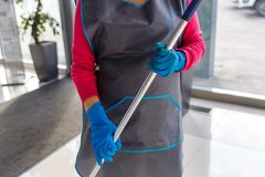 Charwoman in apron and gloves, cleaning. Company stock photography