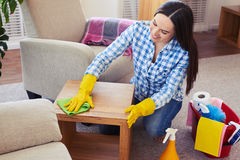 Charwoman carefully cleaning with mop small coffee table. Mid shot of charwoman carefully cleaning with mop small coffee table royalty free stock image