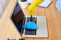 Charwoman dusting with small broom keyboard Stock Image