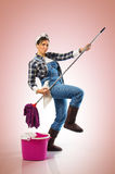 Charwoman on Pink. Cheerful woman with mop and bucket ready to clean the floor on pink background royalty free stock images