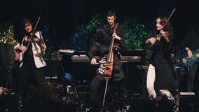Charyzmatyczny dziewczyna wiolonczelista bawić się i tanczy na scenie jako część chłodno zespołu rockowego Artystyczne dziewczyny zbiory wideo