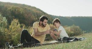 Charyzmatyczny mężczyzna bawić się z jego synem kłaść w dół na trawie i wydaje śmiesznego czas wpólnie przy naturą zbiory wideo